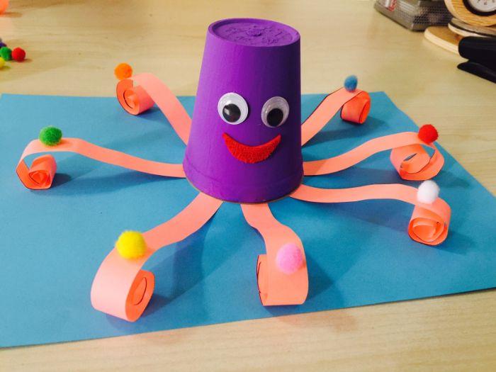 pieuvre fabriquée dans gobelet en plastique repeint de violet avec des tentacules de papier et de syeux mobiles, activité manuelle été