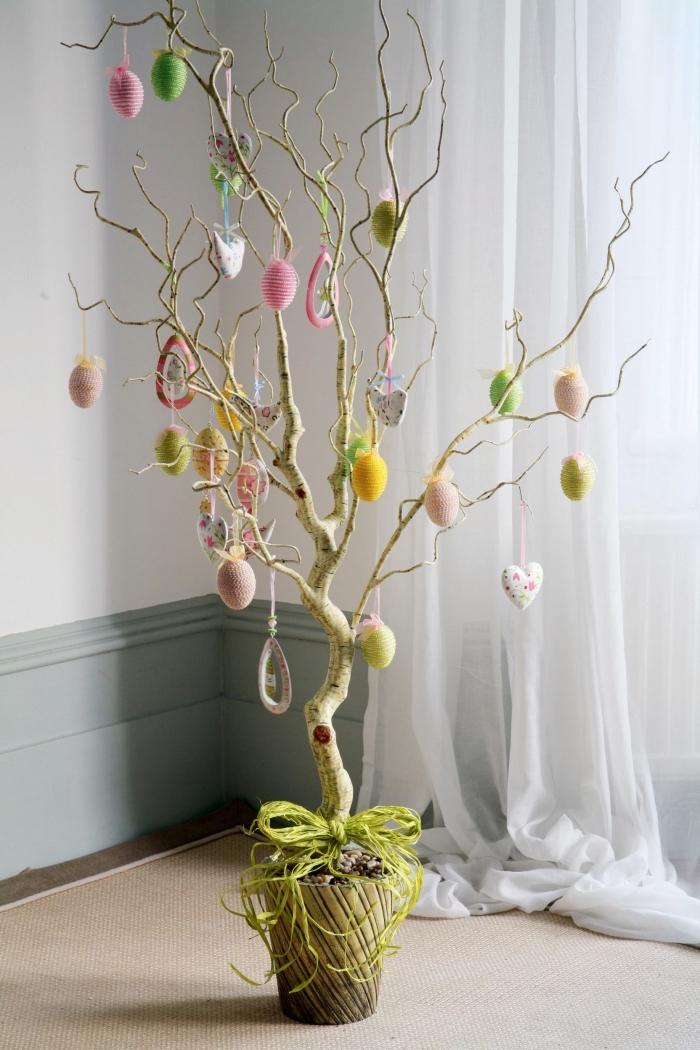 idée activité de paques pour grands et petits, modèle arbre décoré d'oeufs de Pâques dans un pot décoré avec ruban vert