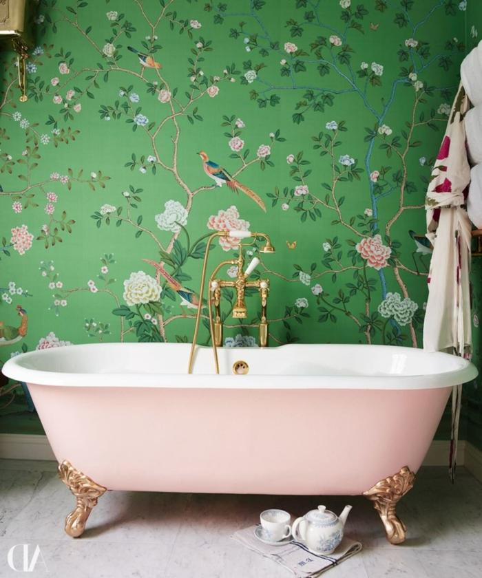 Belle salle de bain avec baignoire rose ovale détails dorés, papier peinte arbres fleuries et oiseaux, peinture vert de gris, salle de bain colorée revetement carrelage