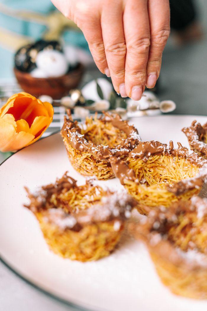 saupoudrer les nids de flocons de noix de coco au chocolat, idée de dessert de paques a faire soi meme