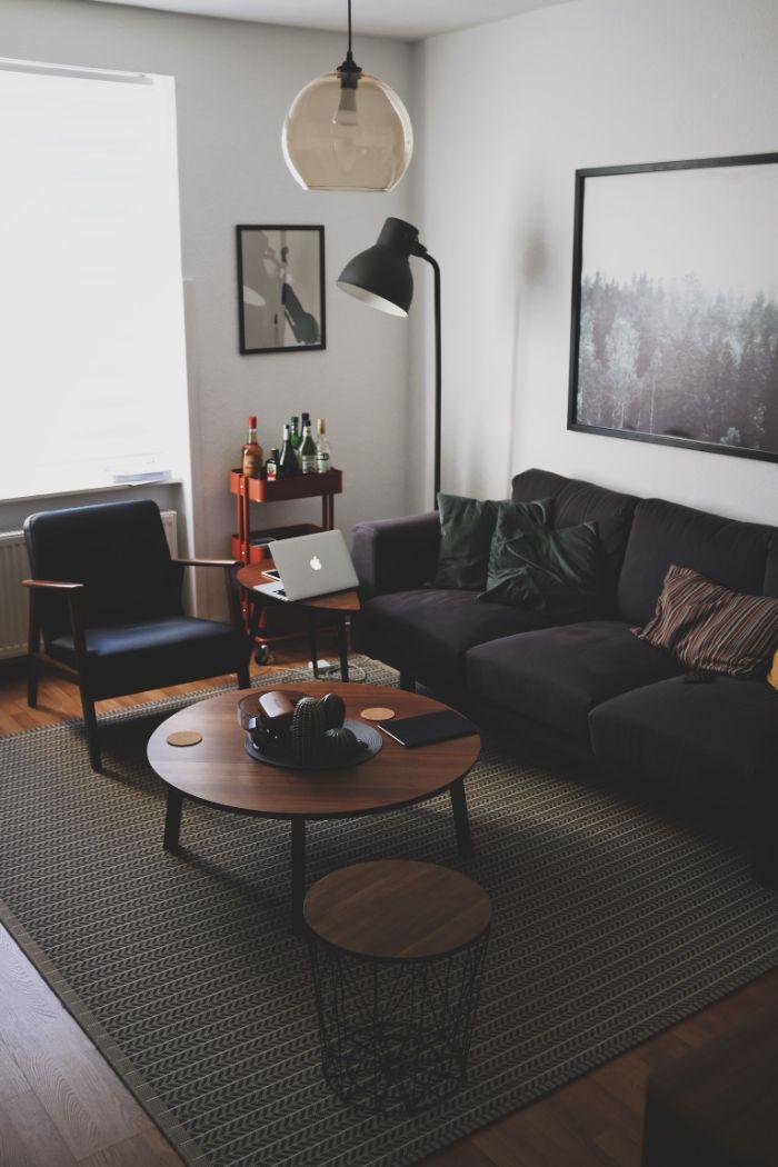 amenagement salon gris anthracite et blanc avec table basse ronde de bois au centre sur parquet bois foncé