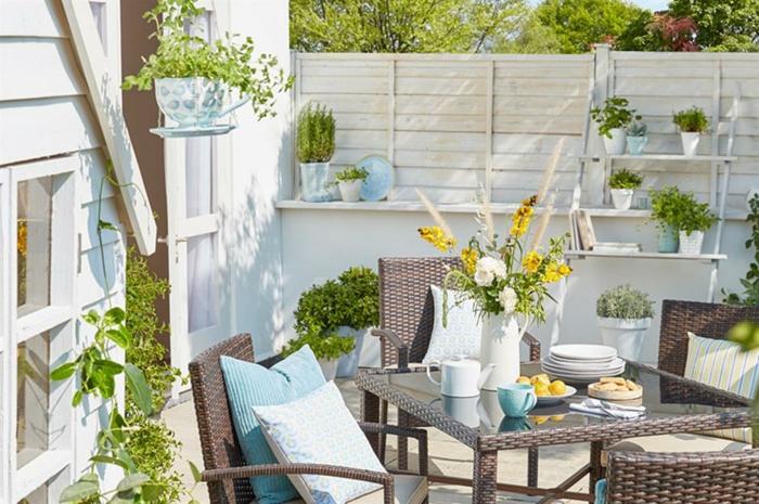 Table et chaises déco jardin coussins bleus, vase et pots fleuries, idees terrasses exterieures, amenagement petit jardin moderne