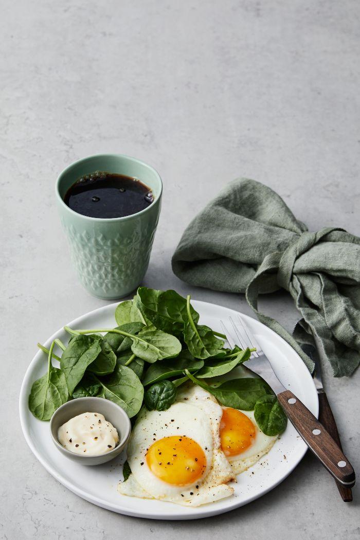 idee de petit dejeuner simple rapide et équilibré, oeufs, épinards et mayonnaise dans assiette blanche