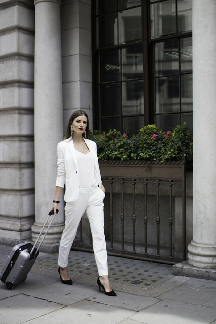 Comment s'habiller pour voyager, tailleur blanc pour femme, ensemble tailleur femme chic valise gris