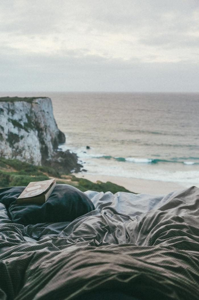 Lire un livre au bord de la mer sur son couverture confortable, fond d écran hiver, fond d écran cocooning photo cosy vibrations