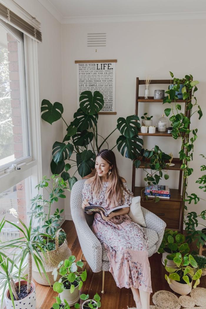 Femme qui lit un livre dans son coin lecture bohème style, plantes vertes, aménagement petit appartement 40m2, idée déco appartement moderne