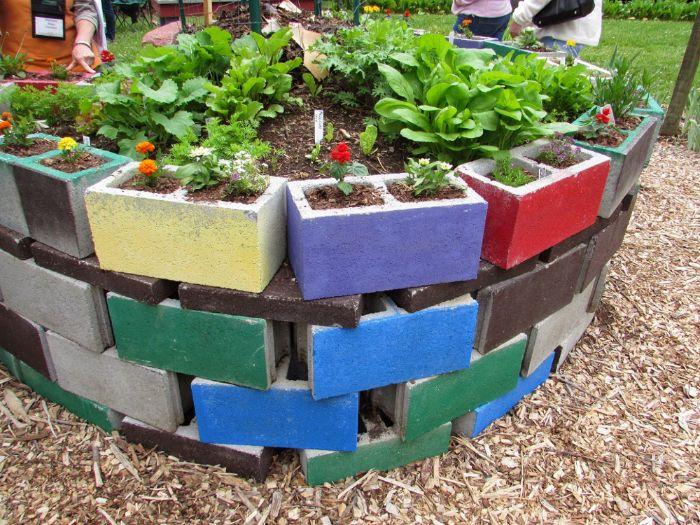 comment faire un jardin exterieur, lit de fleurs composée de jardinieres de beton repeintes de couleurs variées