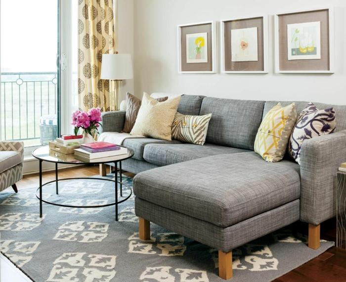 Grand canap\e en angle et petite table ronde pour le salon aménagement petit appartement, décoration appartement étudiant