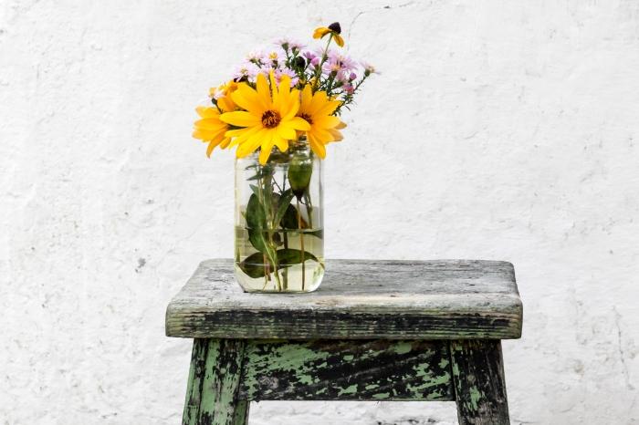 idée créative pour décorer sa maison avec objets recyclés, modèle de vieux bocal en verre transformé en vase sur tabouret en bois