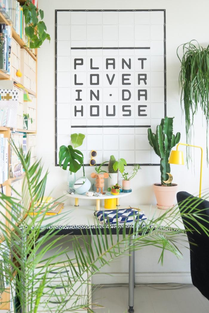 design intérieur de style jungalow dans un petit coin de bureau aux murs blancs avec meubles en bois et plante tropicale