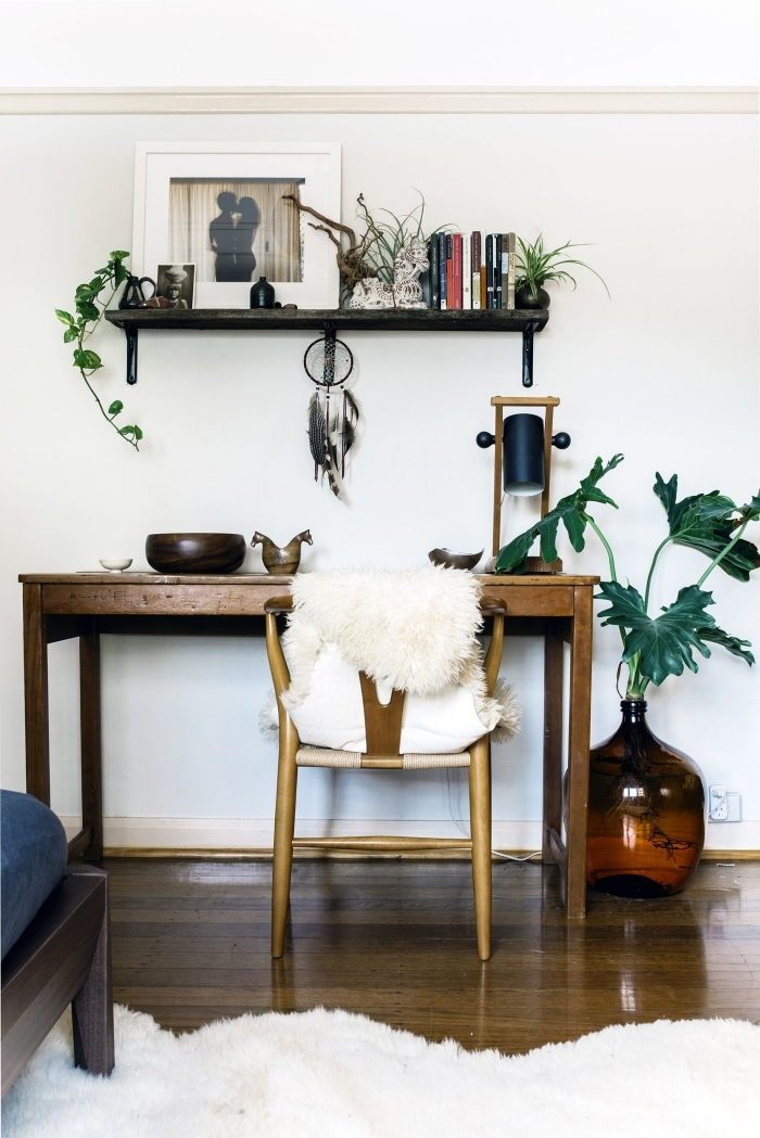 ambiance chic dans un salon bohème aménagé avec meubles en bois foncé et décoration avec petites plantes vertes et plante tropicale