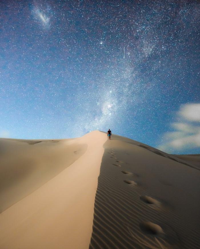image fond d écran pour téléphone portable, photo voyage avec un homme qui se promène dans le désert sous ciel étoilé