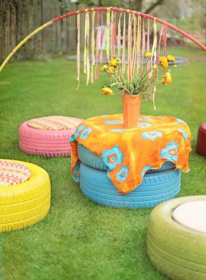 recyclage pneu pour fabriquer un salon de jardin en pneus repeints avec table et tabourets en pneus en plein air