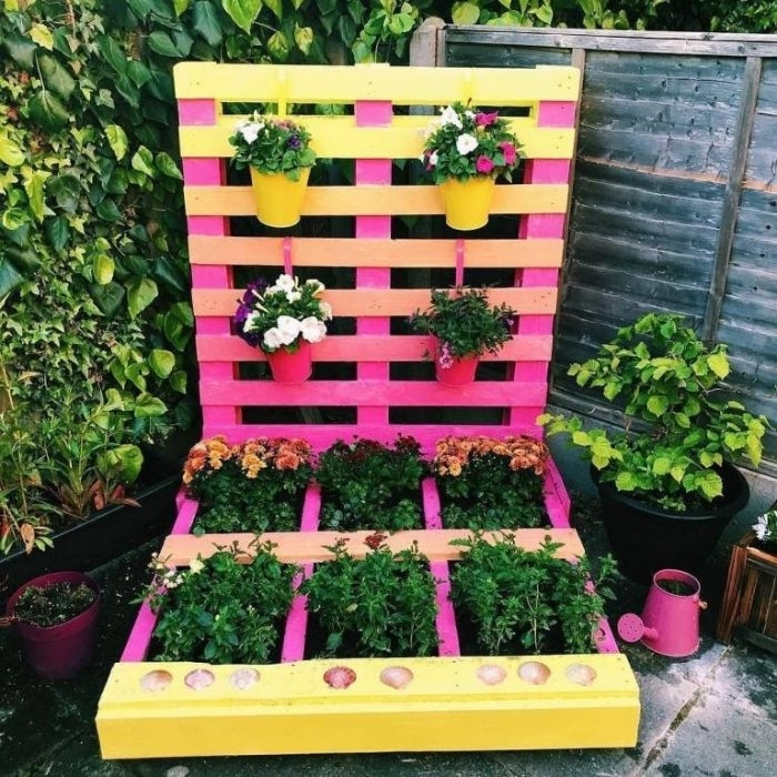 fabriquer une jardiniere en palette soi meme dans palette recyclée et repeinte de jaune et rose avec pots accrochés