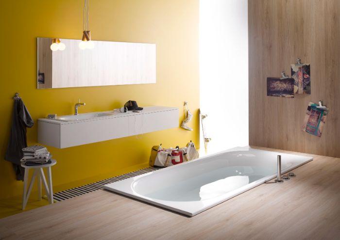 peinture murale salle de bain couleur jaune avec miroir rectangulaire et meuble blanc, revetement sol bois, baignoire encastrée dans le sol