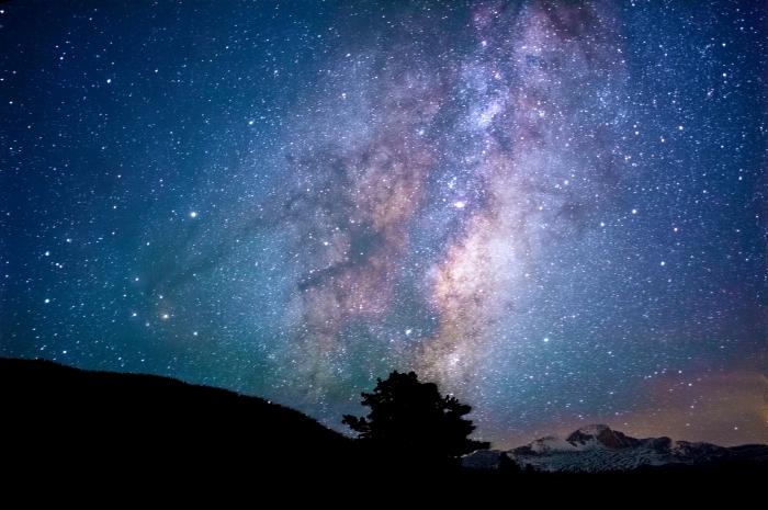 fond d écran stylé pour personnaliser son ordinateur, image galaxie avec ciel nocturne et silhouette de montagnes et arbre