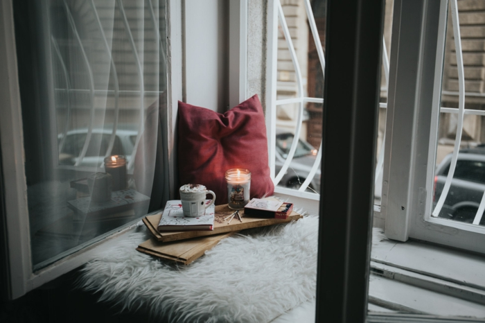 Endroit cocooning coin avec bougie et livre, boire un chocolat chaud pres du fenetre photo cocooning