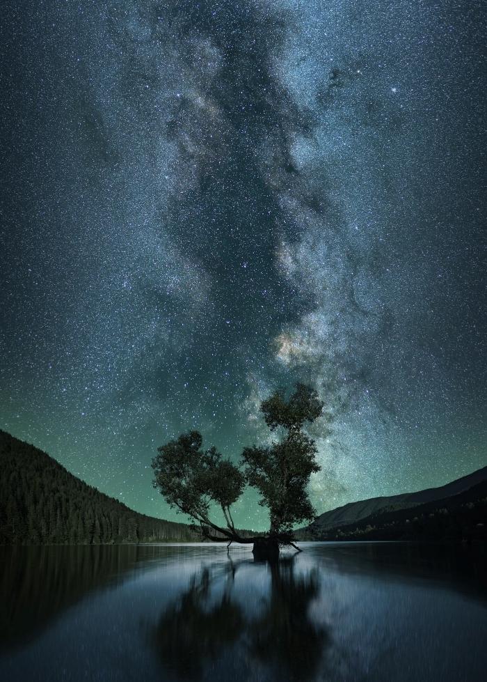 paysage fond d écran nocturne avec sommets de montagnes et reflets de silhouettes d'arbres dans un lac sous le ciel étoilé