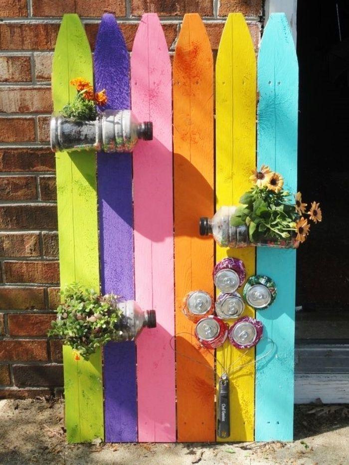 recyclage bouteilles en plastique transformées en pots de fleurs et une fleur en canettes de boisson recyclées sur mur de palette coloré