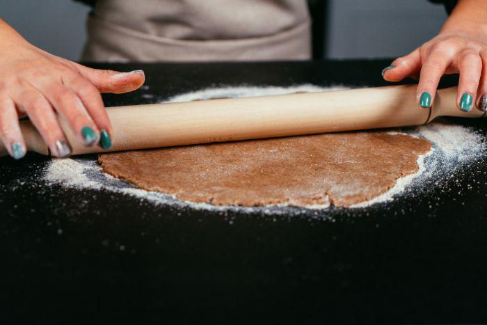 se servir de rouleau à patisserie pour étaler la pâte de tarte aux pommes sur surface plate, idee dessert leger aux pommes