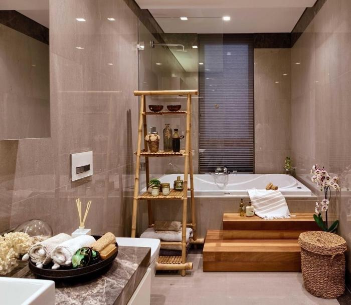 agencement petite baignoire dans une salle de bain zen aux murs gris clair décorée avec accents en bois et fibre végétale