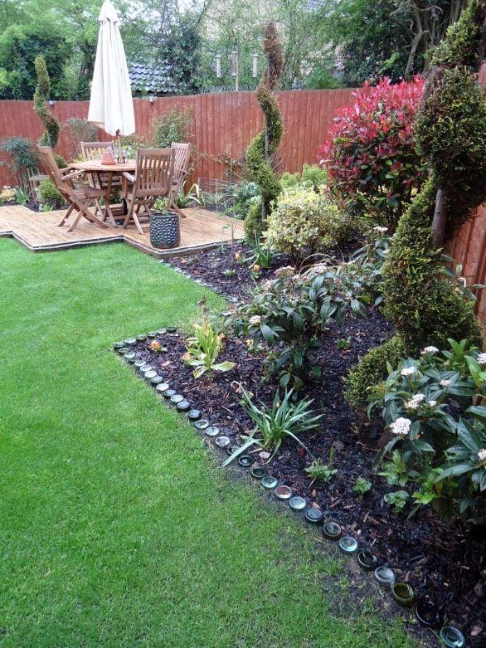 exemple de deco jardin a faire soi meme avec une palte bande bordée de bouteilles de verre plantées dans le sol, idée bordure de jardin récup