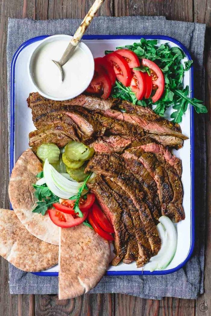 recette barbecie originale fajitas de boeuf avec sauce yaourt servis avec pain plat, roquette et tomates en tranches