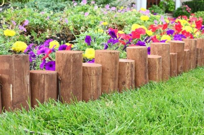 alignement de buches de bois traité pour border une parte de fleurs, idee deco jardin rustique bordure de bois