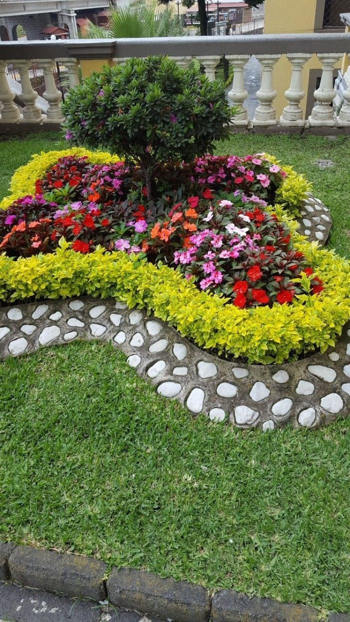 parterre de fleurs originale en forme de papillon avec bordure de pierre sur un gazon, bordure originale