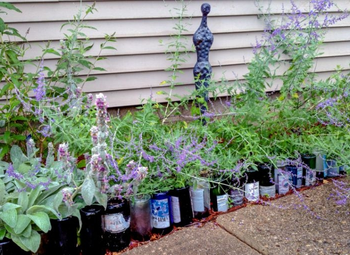 bouteilles de vin recyclées pour faire une bordure exterieur et separer parterre d une allée de jardin