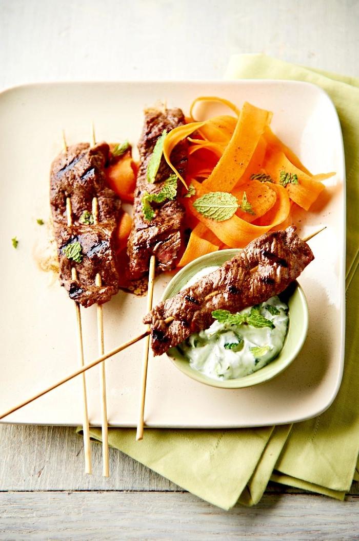 idee brochette de viande grillée de boeud à la sauce tzatziki et des carottes dans une assiette blanche