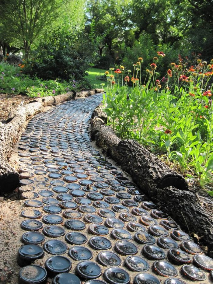 chemin de jardin en bouteilles de verre de vin renversées et plantées dans le sol et bordure jardin bois en tronc d arbre