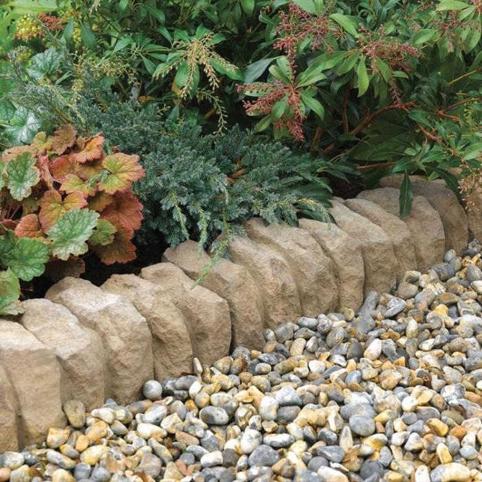 bordure de jardin en pierre et galets pour separer une plate-bande de plantes vertes dans jardin