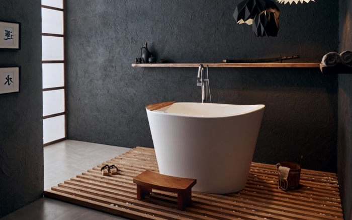 modèle de petite baignoire blanche sur tapis bois, décoration salle de bain de style asiatique relax aux murs foncés et accents bois