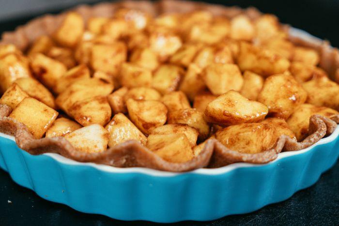 verser les cubes de pommes à la cannelle dans la plaque à tarte, idée dessert aux pommes americain, tarte aux pommes maison