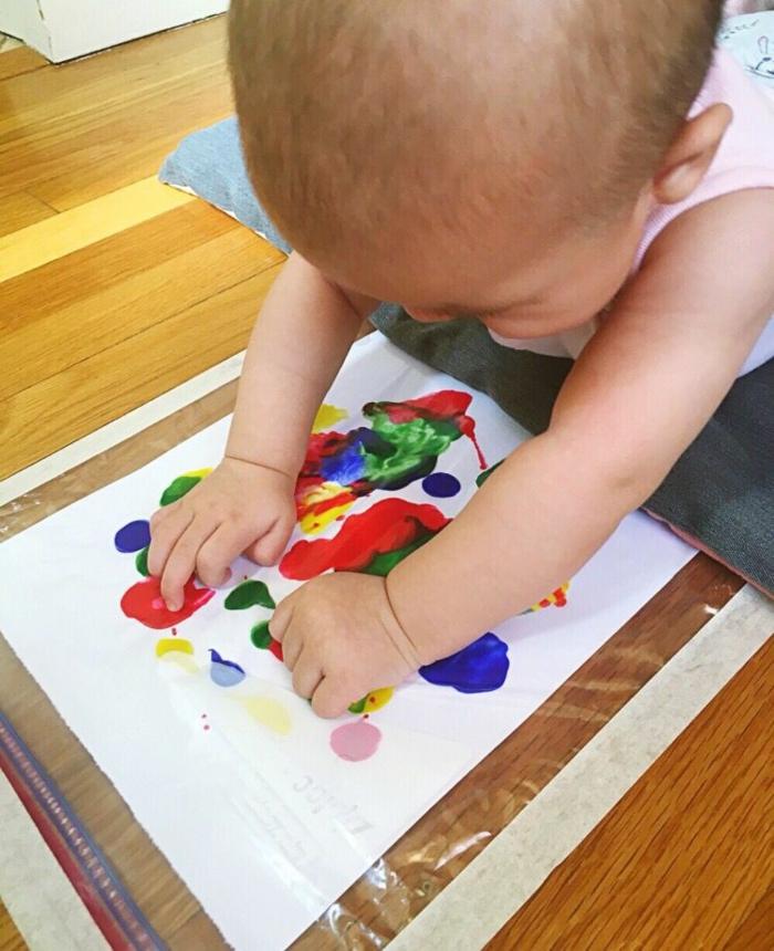 Aider son bébé à faire sa premiere peinture coloré, cool idée cadeau fete des peres original, bricolage fête des pères pour tout petit