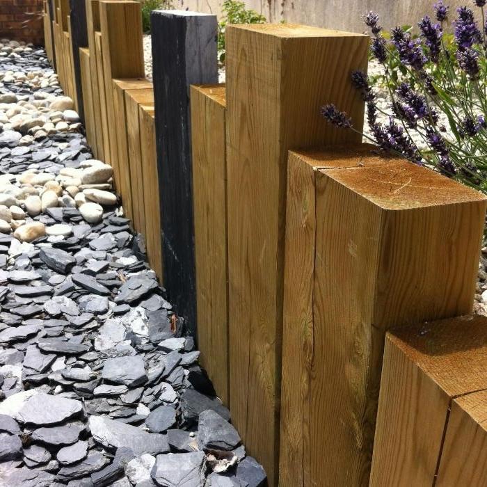 bordure bois a planter constitué de blocs de bois de tailles variées avec des galets, bordure allée bois récup