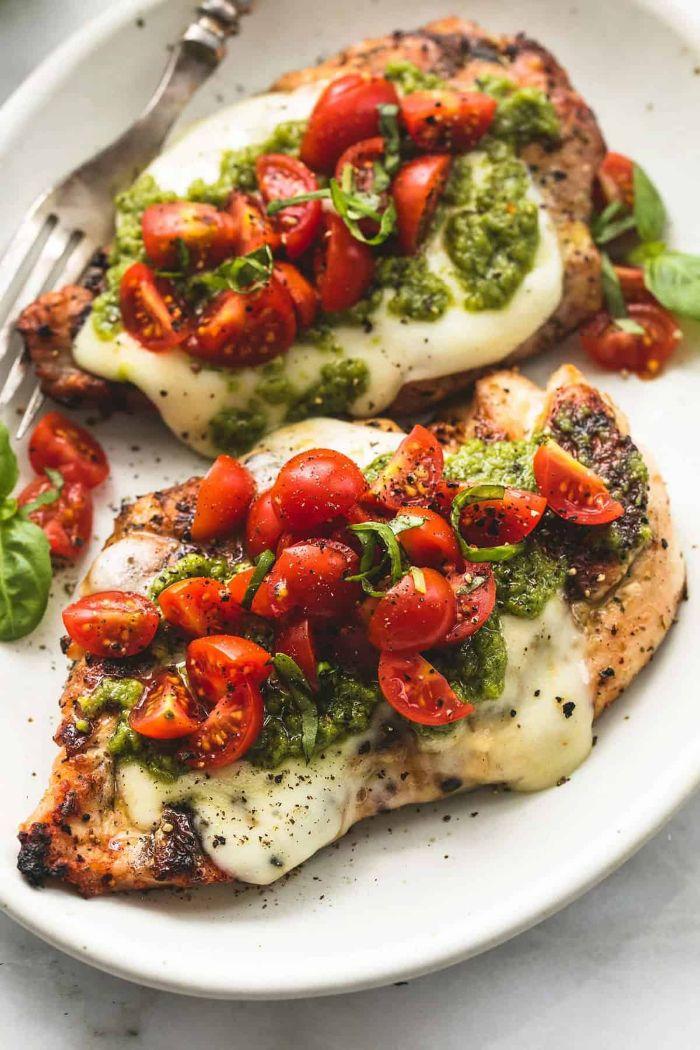 idée de recette avec blanc de poulet avec du fromage fondu en top, des quartiers de tomate cerise et pesto