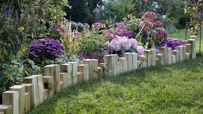 blocs de bois plantés dans les sol à hauteur différente pour fabriquer une bordure jardin bois rustique