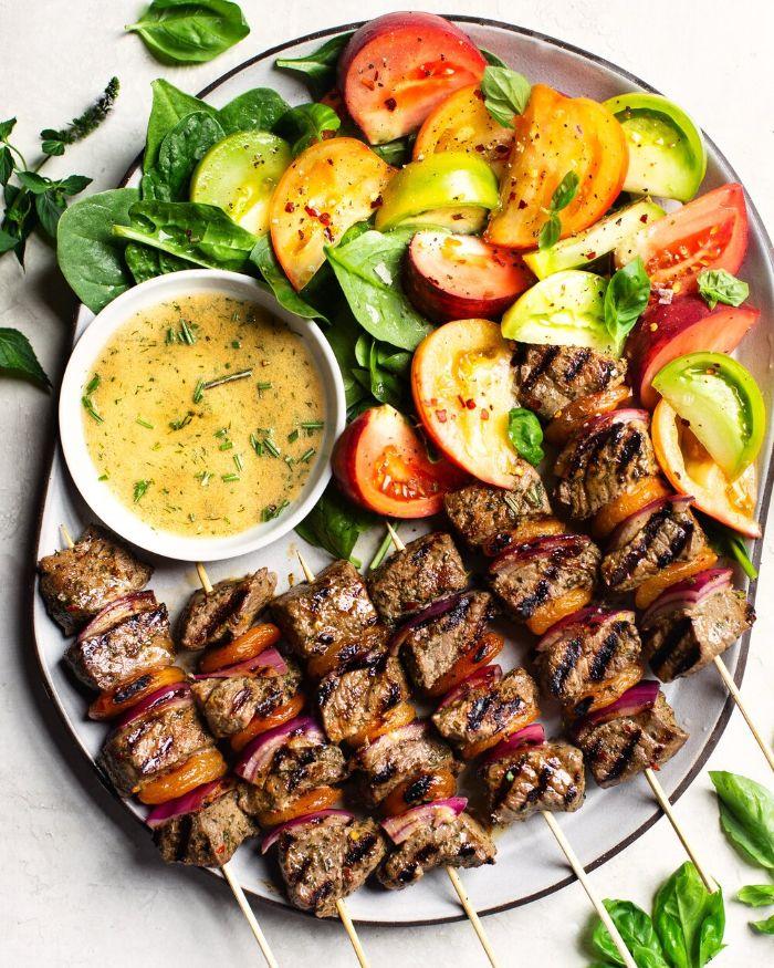 salade aux épinards bébés et des tomates comme idée accompagnement de brochettes de boeuf aux oignons et poivrons avec de la sauce,