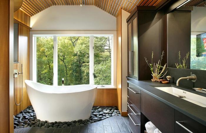 agencement salle de bain asiatique avec petite baignoire autoportante sur un jardin aux cailloux gris, déco salle de bain en blanc gris et bois
