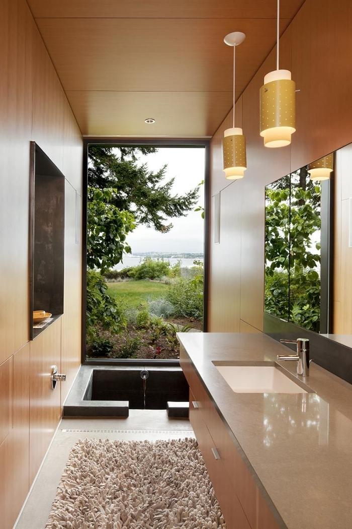 design petite salle de bain de style asiatique avec murs à effet bois, modèle de petite baignoire pierre noir de style japonais