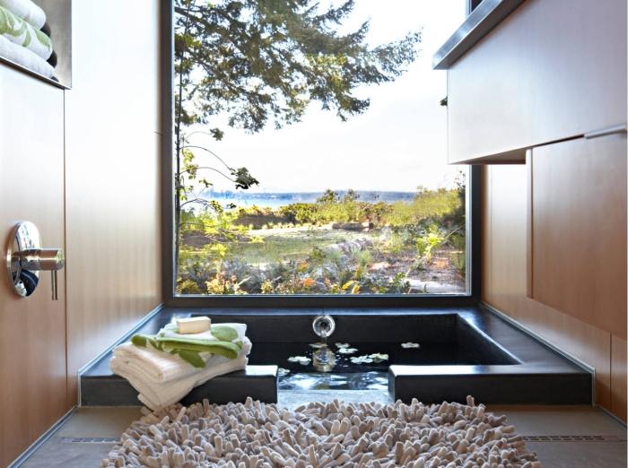 idée comment décorer une petite salle de bain nature avec baignoire noire, design salle de bain aux murs en bois et sol gris