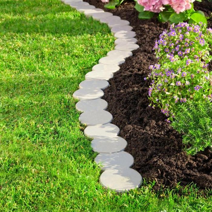 galets plats en forme ronde à aligner pour fabriquer une bordure de jardin et separer une parterre de fleurs
