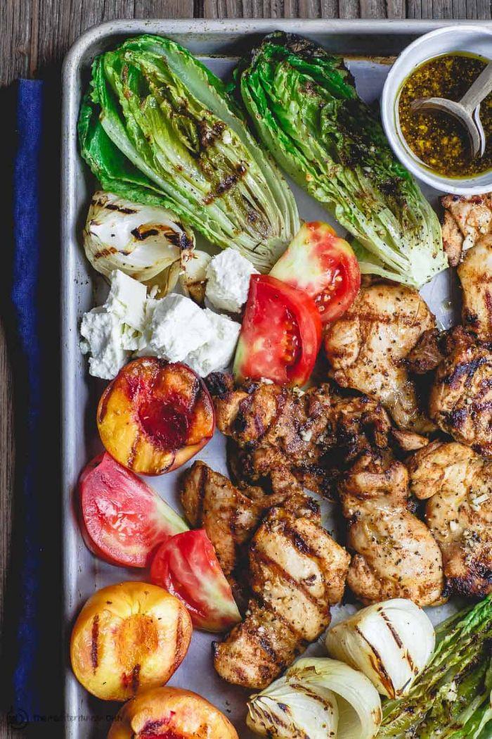 grillade barbecue simple constituée de poulet à la salade verte, tomates et pêches rôtis au four et servis avec pesto
