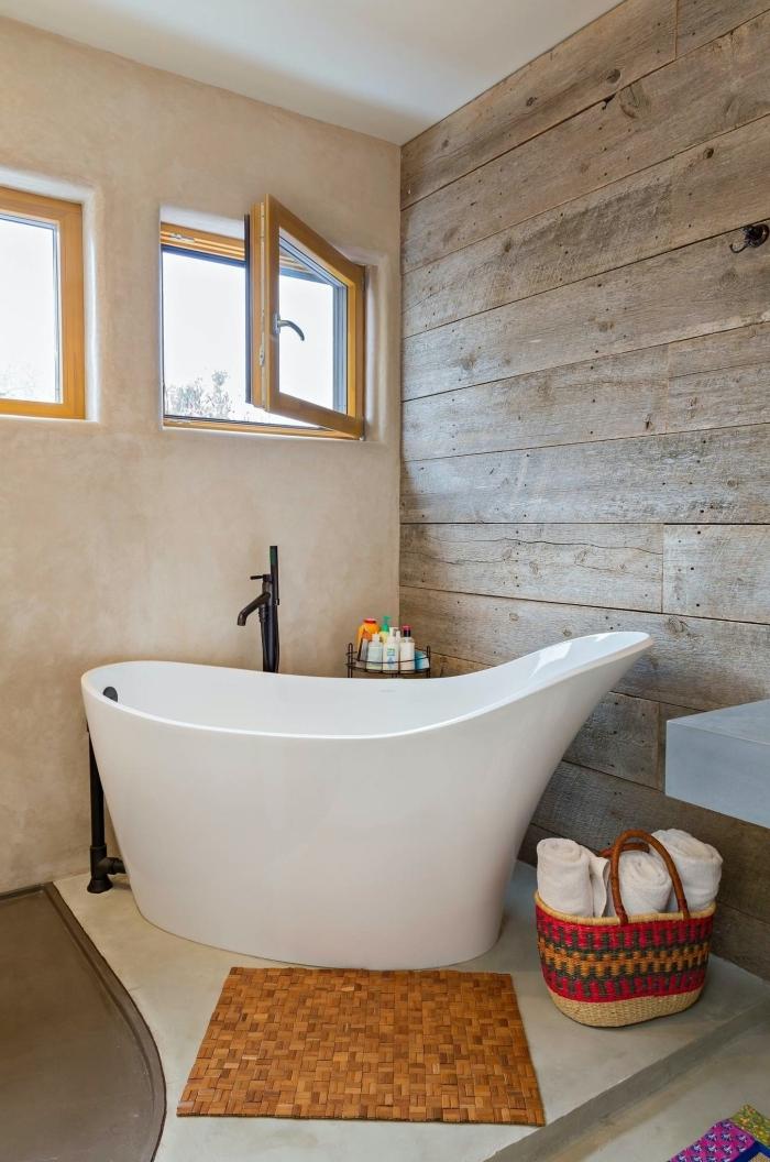 modèle de baignoire sabot autoportante dans une petite salle de bain aux murs à effet bois et sol en blanc et gris