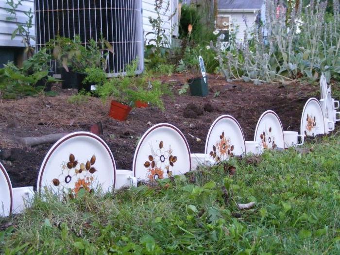 deco jardin recup originale avec de la vaisselle vintage en assiette à motif fleuri et des tasse de thé blanches