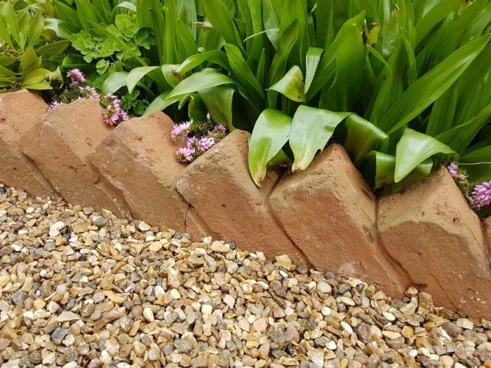 alignement de briques en biais pour faire une bordure massif diy recup planté dans gravier