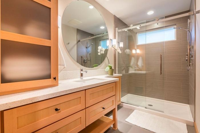 design salle de bain bois et blanc avec cabine de douche, décoration petite salle de bain avec grand miroir rond et fleurs