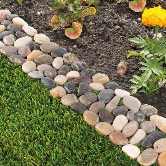 bordure de galets de couleurs variées pour séparer un gazon d un parterre de fleurs, idee deco jardin recup